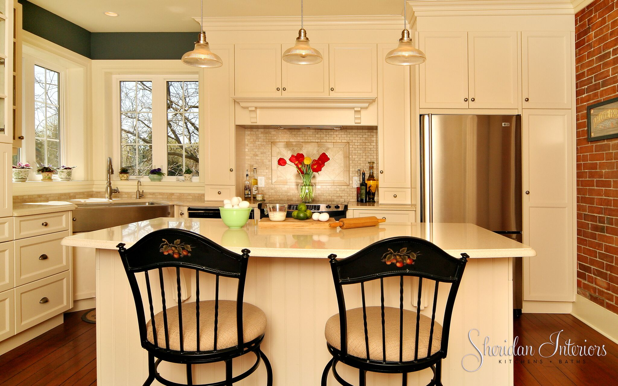 country kitchen, farmhouse kitchen, white country kitchen, farmhouse sink, stainless steel farmhouse sink, corner sink, apron front sink, marble brick backsplash brick wall in kitchen, white countertops, kitchen with wood floors, hardwood floors in kitchen, kitchen designer cornwall, kitchen designer ottawa, kitchen designer finch, interior designer cornwall, interior designer ottawa, schoolhouse pendants, kitchen designer cornwall, kitchen designer ottawa, interior designer cornwall, interior designer ottawa, 1800's Redux Gallery - Sheridan Interiors, sheridan interiors kitchens and baths, sheridan interiors