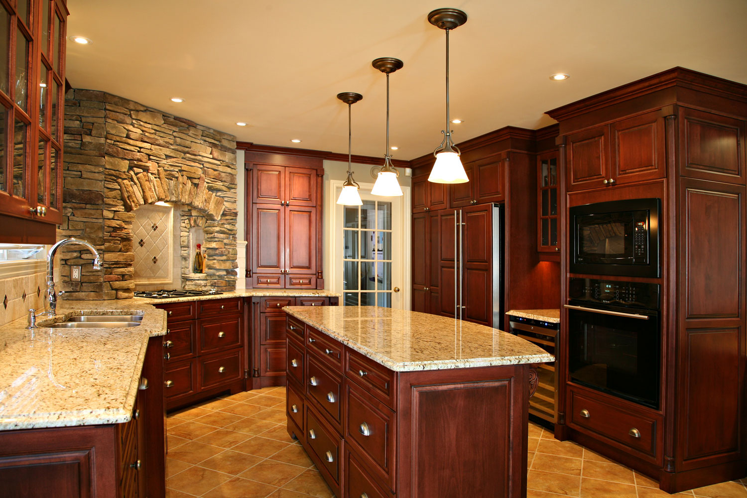Traditional kitchen with island, corner gas cooktop with stone surround and wine station - Sheridan Interiors