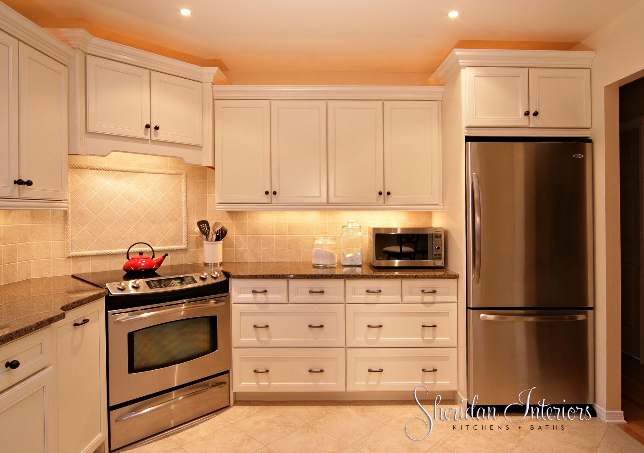 White kitchen with corner stove, countertop microwave and stainless steel fridge - Sheridan Interiors