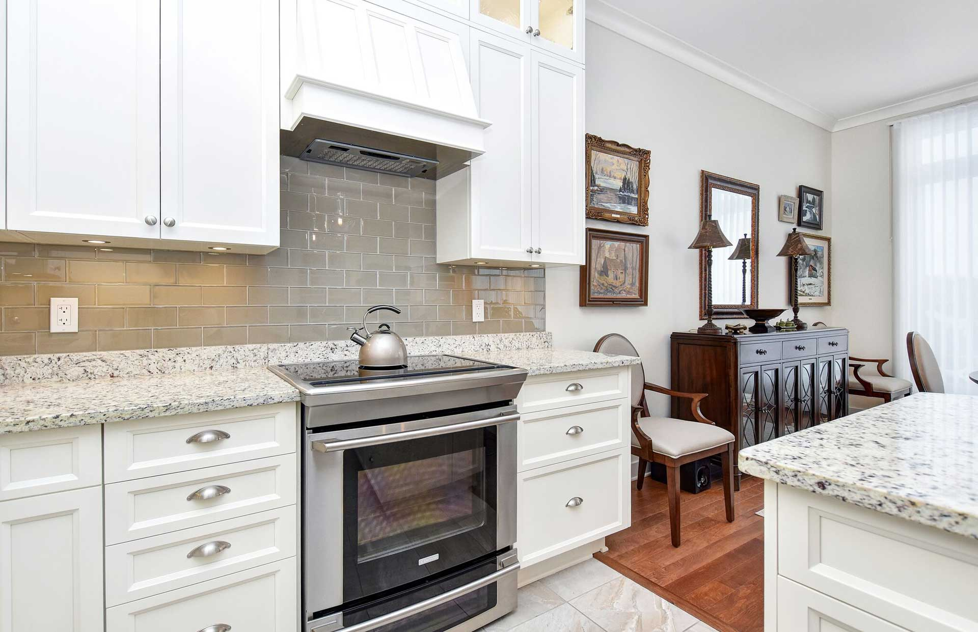 condo living, condo kitchen, shaker cabinets, granite countertop, glass subway tile backsplash