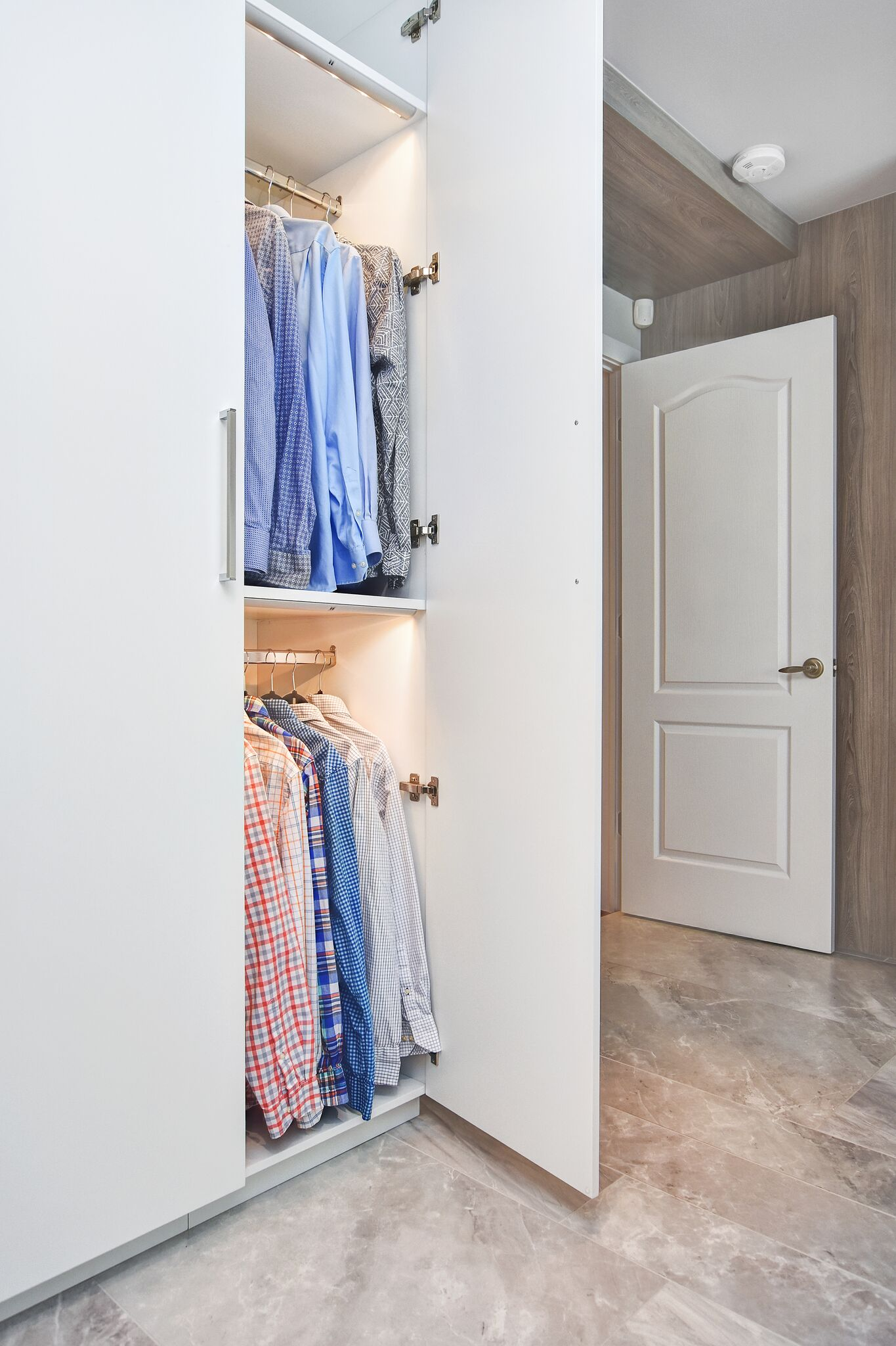 reach in closet with interior lighting and double rods